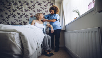 Caregiver and Older woman in bed