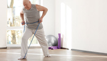 elderly man exercising with resistance bands