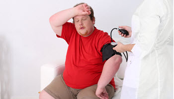 obese man getting blood pressure checkup